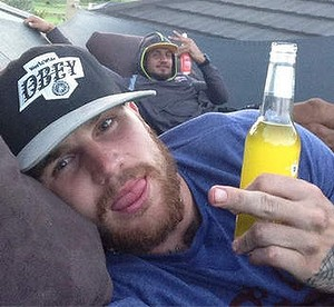 Josh Dugan drinking on a roof